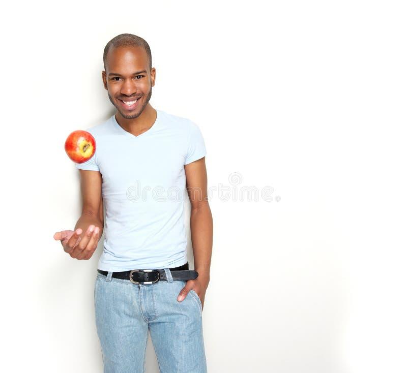 Uomo sorridente con la mela fotografie stock