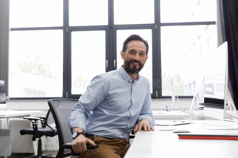 Uomo sorridente di affari maturi che si siede nel suo luogo di lavoro fotografia stock libera da diritti