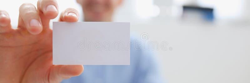 Uomo sorridente di affari nello spazio in bianco della tenuta del vestito a disposizione immagine stock libera da diritti
