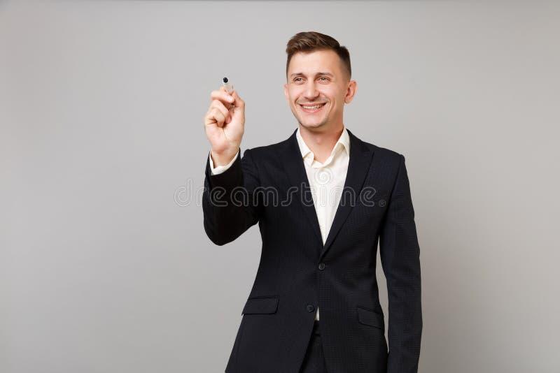 Uomo sorridente di affari in vestito nero che attinge parete virtuale, scrivente con la penna di indicatore nera sullo schermo vi fotografia stock libera da diritti