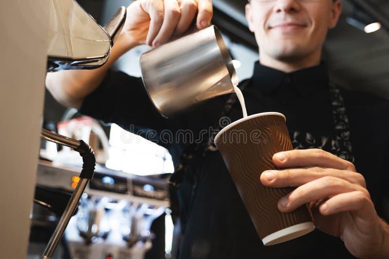 Uomo sorridente di barista che versa latte montato dallo schiumare lanciatore in tazza di carta con caffè che sta davanti a immagini stock