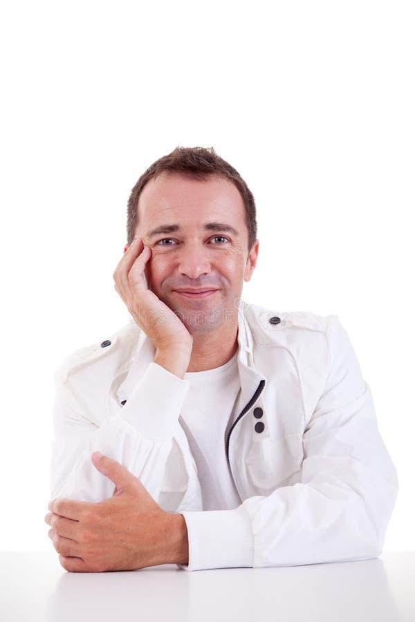 Uomo sorridente di centrale-età che si siede allo scrittorio fotografia stock libera da diritti