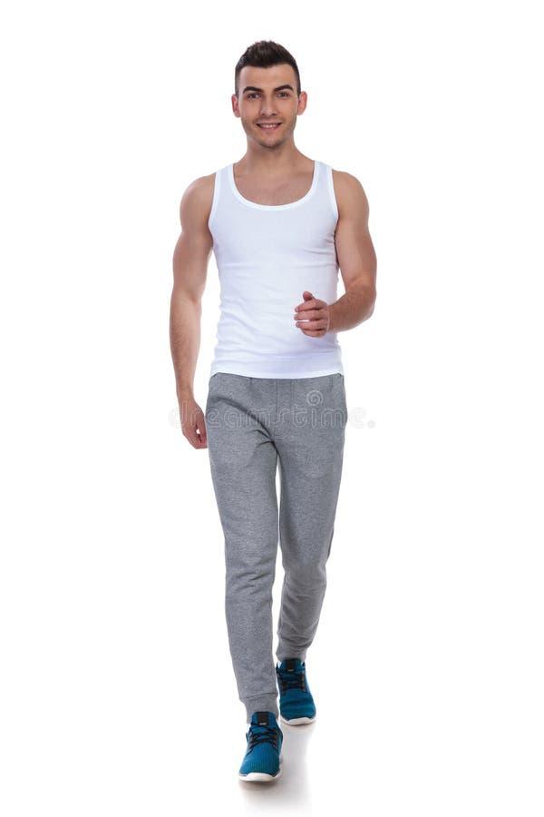 Uomo sorridente di forma fisica nella camminata bianca della maglietta fotografie stock libere da diritti
