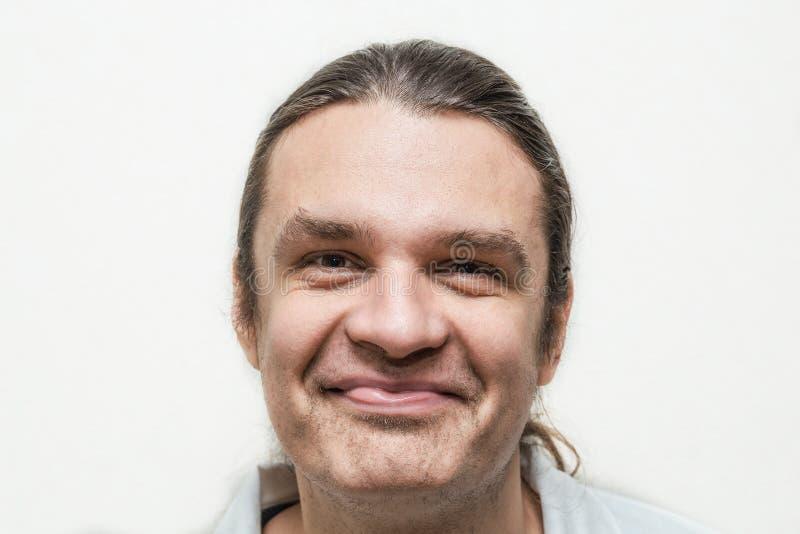Uomo sorridente divertente che esamina macchina fotografica su fondo bianco fotografia stock
