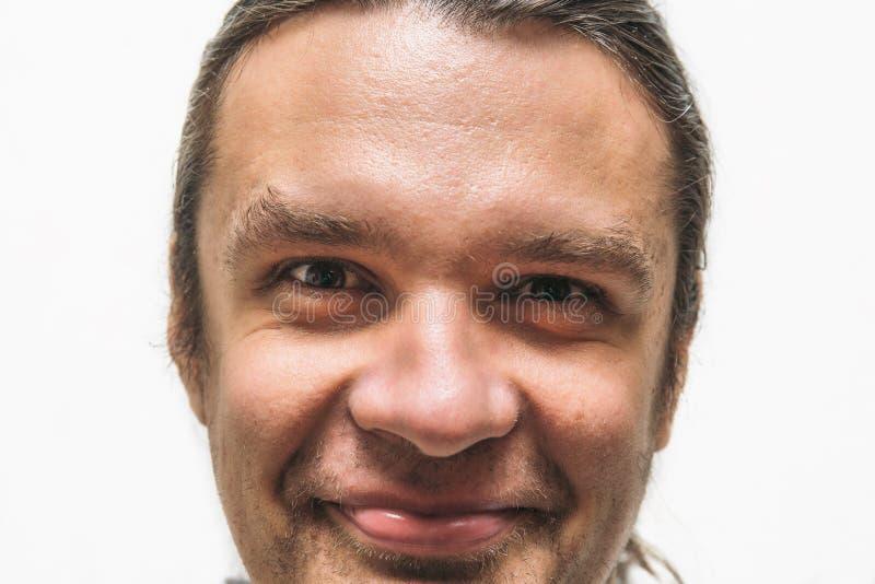 Uomo sorridente divertente con gli occhi pazzi che esaminano macchina fotografica su fondo bianco fotografie stock libere da diritti