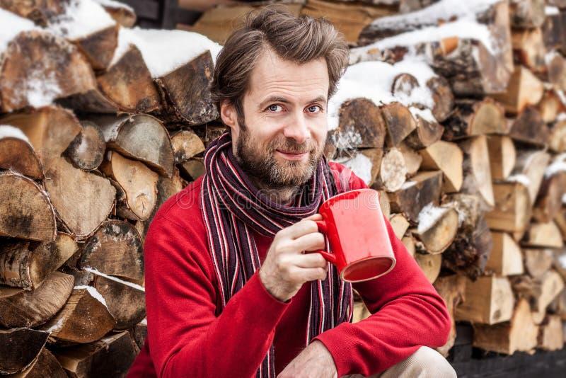 Uomo sorridente felice che beve tè caldo all'aperto - paesaggio della campagna di inverno immagine stock libera da diritti