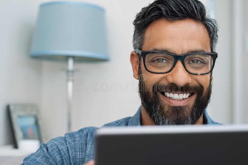 Uomo sorridente felice che lavora al computer portatile fotografia stock libera da diritti