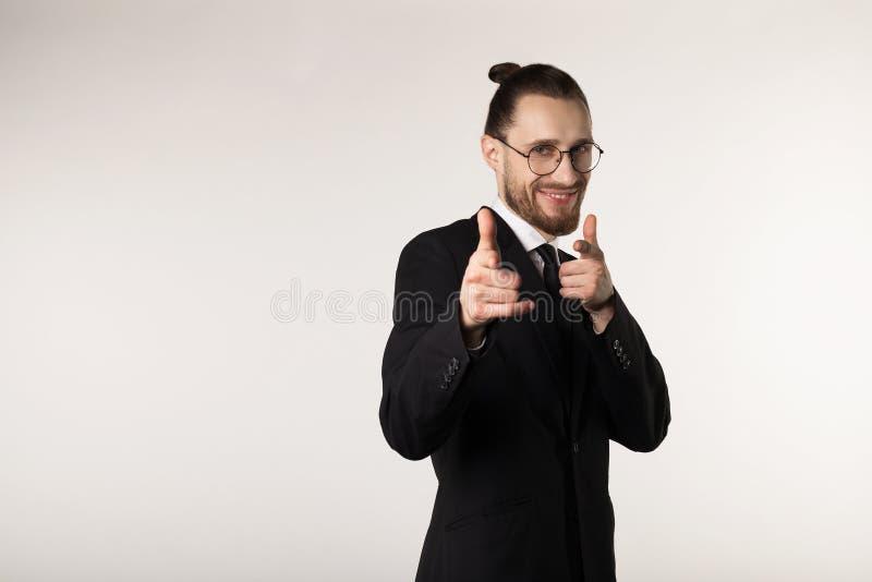 Uomo sorridente felice con la barba e l'acconciatura d'avanguardia che indossano vestito nero e vetri che esaminano e che indican fotografia stock libera da diritti