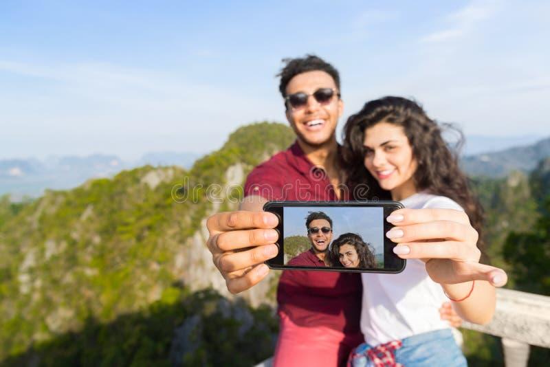 Uomo sorridente felice e donna del giovane delle coppie punto di Mountain View che prendono la foto di Selfie sulla festa dell'as fotografia stock libera da diritti