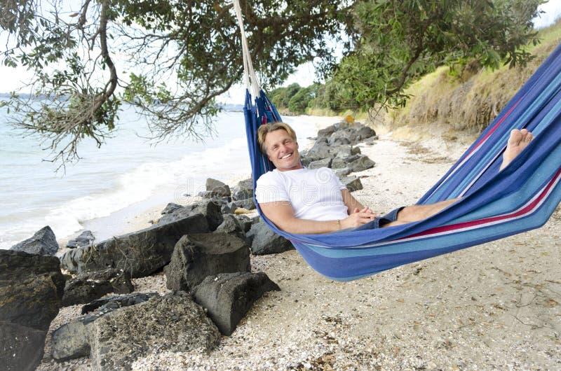 Uomo sorridente felice in hammock fotografia stock
