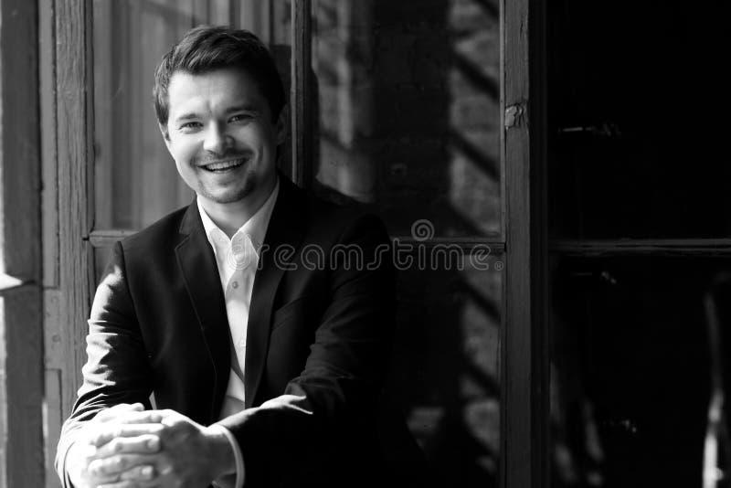 Uomo sorridente felice in vestito nero immagini stock