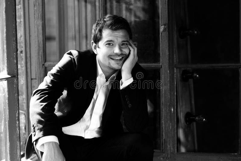 Uomo sorridente felice in vestito nero immagine stock