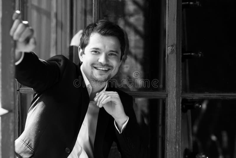 Uomo sorridente felice in vestito nero fotografie stock