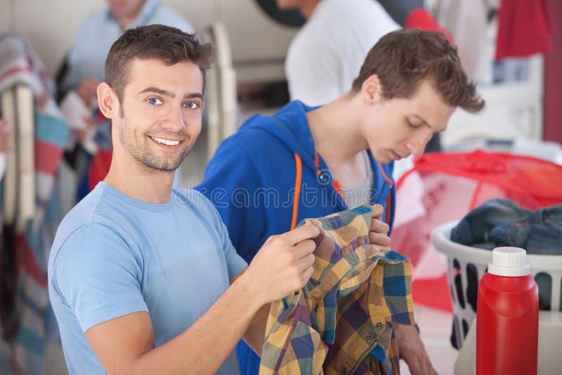Uomo sorridente in lavanderia automatica fotografie stock libere da diritti