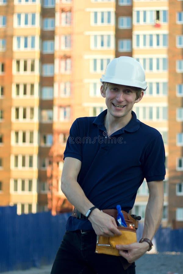 Uomo sorridente nei supporti del casco alla parte anteriore della costruzione di edifici fotografie stock libere da diritti