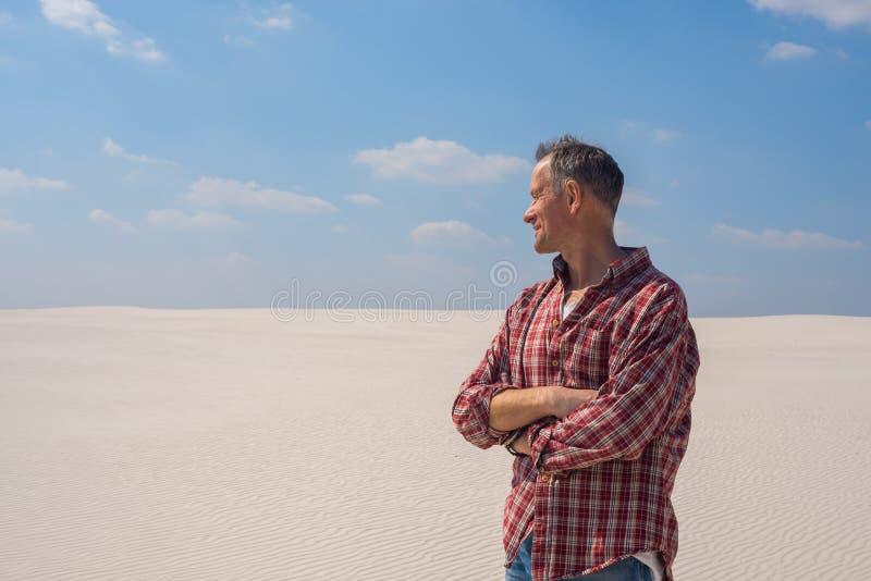 Uomo sorridente nel deserto che ammira il mondo stupefacente del dun della sabbia immagini stock