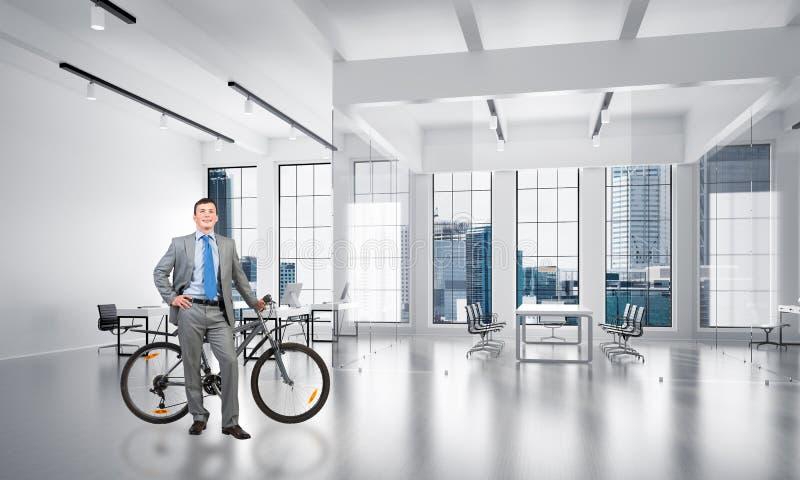 Uomo sorridente nella condizione del vestito con la bici immagini stock
