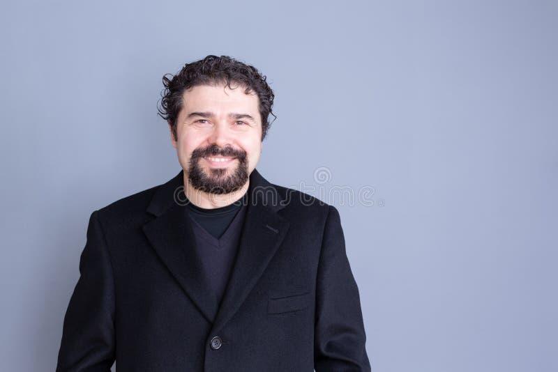 Uomo sorridente in rivestimento nero sopra fondo grigio immagine stock