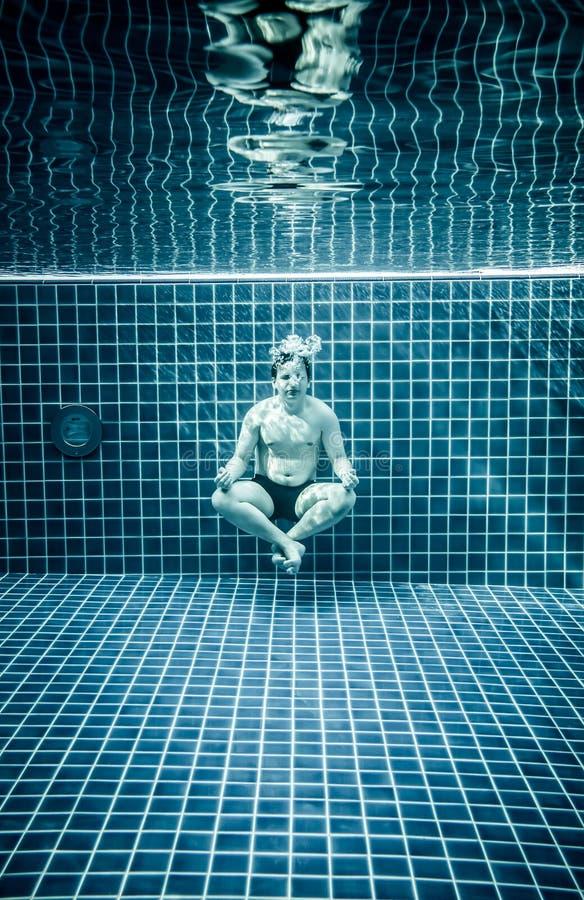 Uomo sotto acqua in una piscina da rilassarsi nel positio del loto immagini stock libere da diritti
