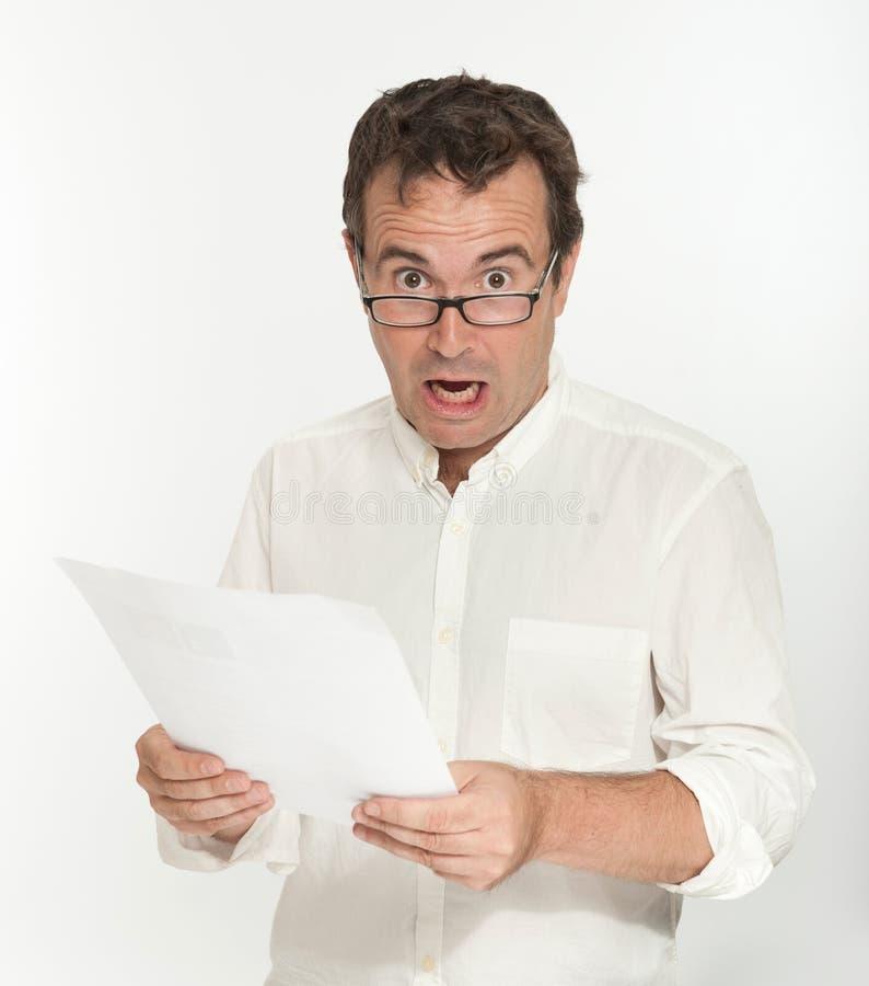 Uomo spaventato che legge un documento fotografie stock libere da diritti