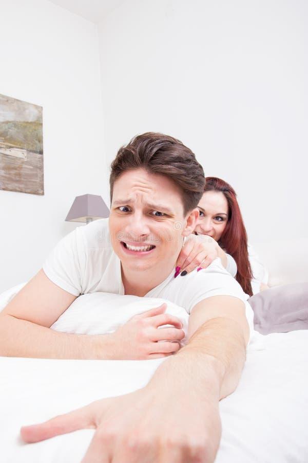 Uomo spaventato che prova a sfuggire a dalla donna fotografia stock libera da diritti