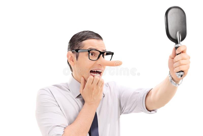 Uomo spaventato con il naso lungo che guarda in uno specchio immagini stock