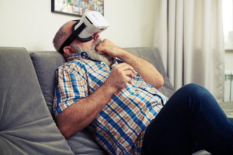 Uomo spaventato a morte facendo uso dei vetri della cuffia avricolare di realtà virtuale immagine stock
