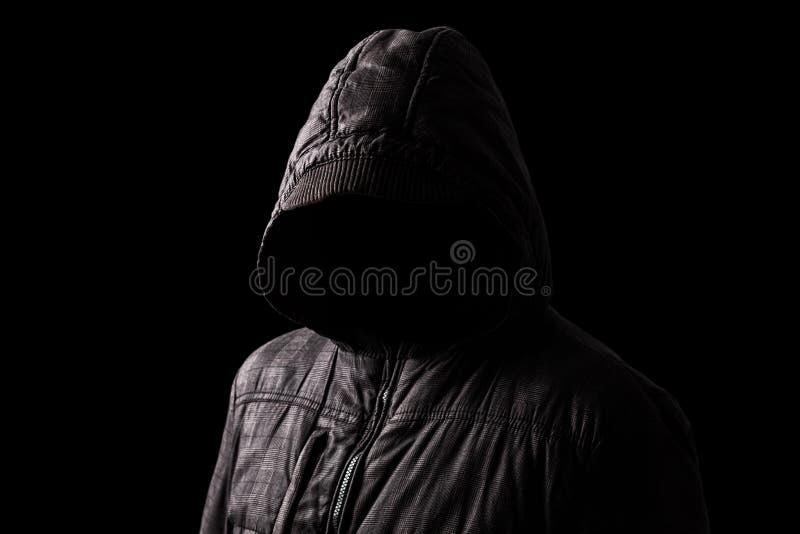 Uomo spaventoso e terrificante che si nasconde nelle ombre, con il fronte e l'identità nascoste con il cappuccio fotografia stock