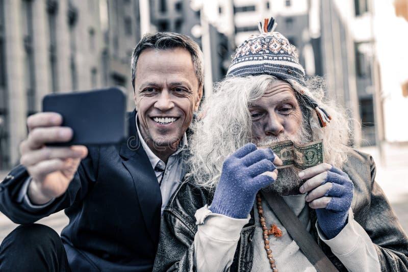 Uomo sporco grigio-dai capelli selvaggio che è messo a fuoco sui soldi in sue mani fotografia stock libera da diritti