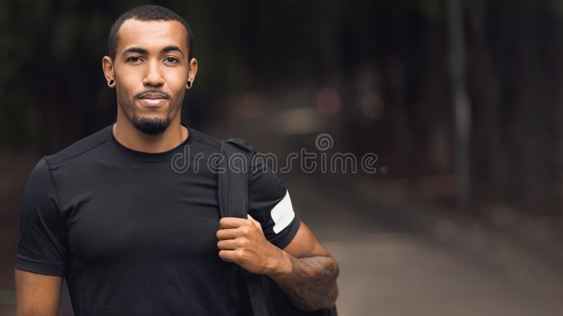 Uomo sportivo che posa dopo l'allenamento, maglietta nera d'uso immagine stock libera da diritti