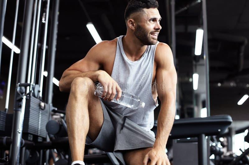 Uomo sportivo che riposa, avendo acqua potabile della rottura dopo avere fatto esercizio immagine stock