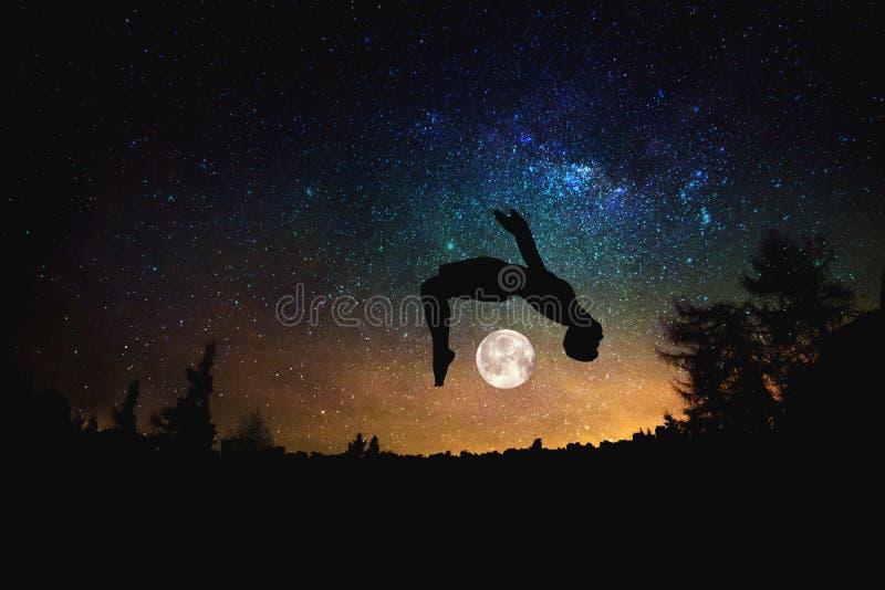 Uomo sportivo che salta contro i precedenti stellati del cielo di notte Media misti fotografie stock