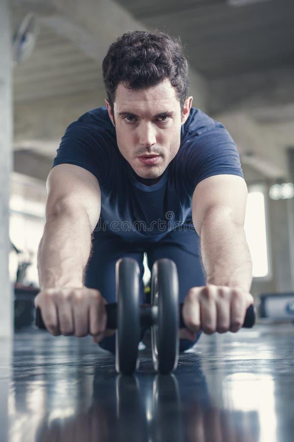 Uomo sportivo dell'atleta che fa esercizio con la ruota del rullo dell'ABS per rinforzare il suo muscolo addominale in palestra fotografia stock libera da diritti