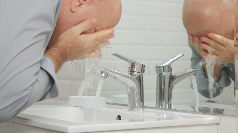 Uomo stanco in bagno che lava il suo fronte con acqua dolce dal rubinetto del lavandino immagini stock