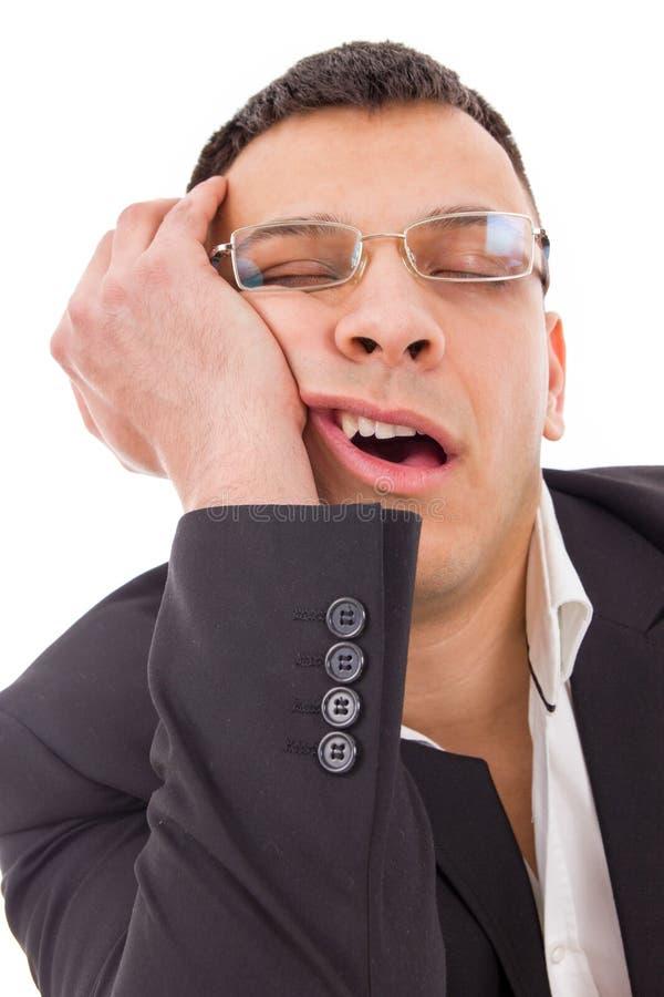 Uomo stanco con i vetri che sbadigliano e che dormono fotografia stock libera da diritti