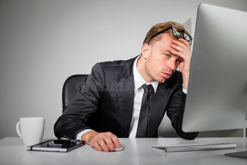 Uomo stanco di affari all'ufficio fotografia stock