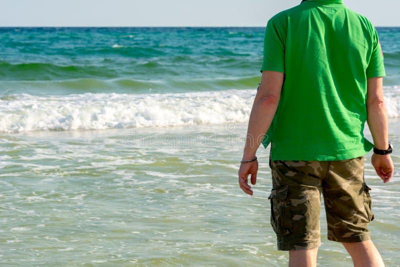 Uomo Standind con riflesso appeso sul collo sul fondo dell'acqua dell'oceano della sfuocatura Spiaggia di Destin, Florida fotografia stock libera da diritti
