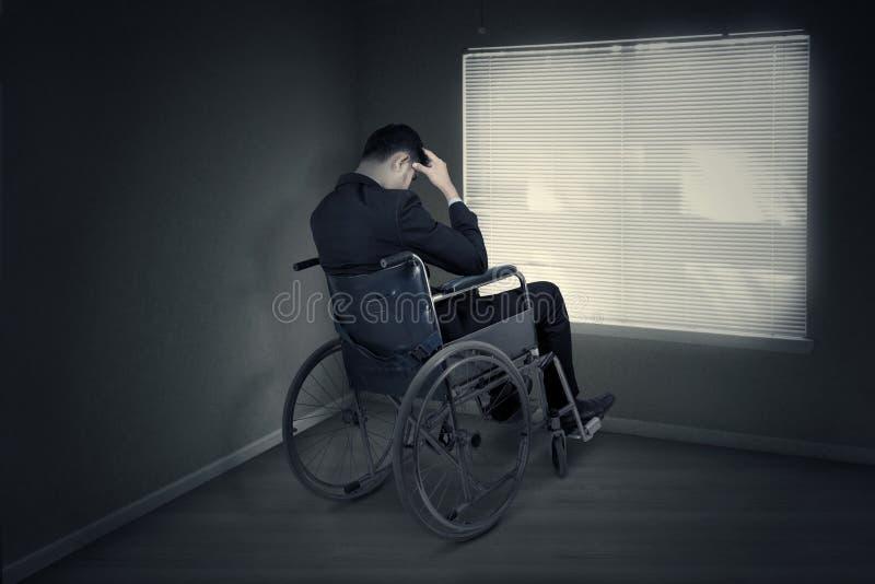 Uomo stressante che si siede sulla sedia a rotelle vicino alla finestra fotografie stock libere da diritti