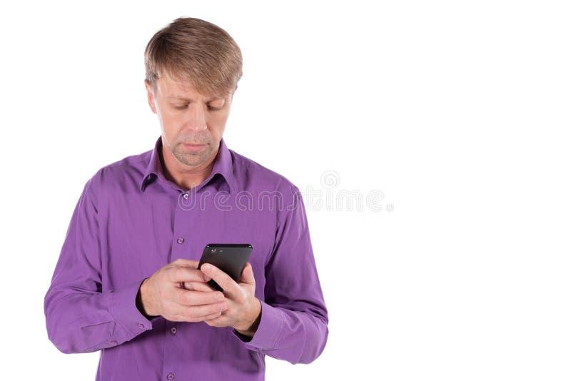 Uomo stupito di medio evo che chiacchiera sul telefono su fondo bianco fotografia stock