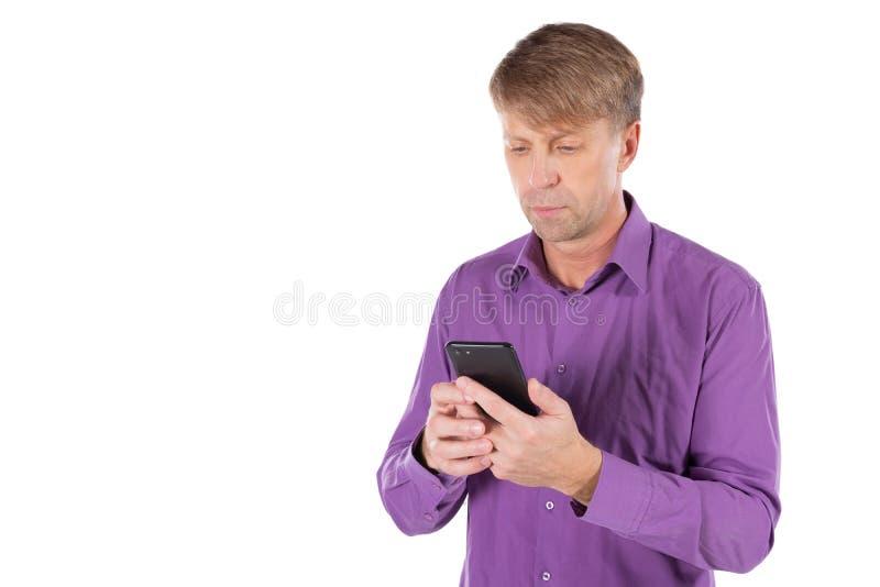 Uomo stupito di medio evo che chiacchiera sul telefono su fondo bianco immagine stock libera da diritti