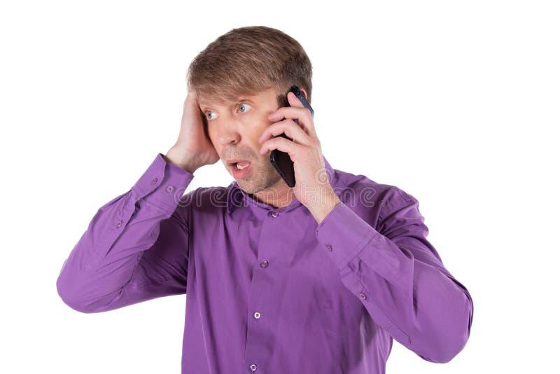 Uomo stupito di medio evo che parla sul telefono su fondo bianco immagini stock