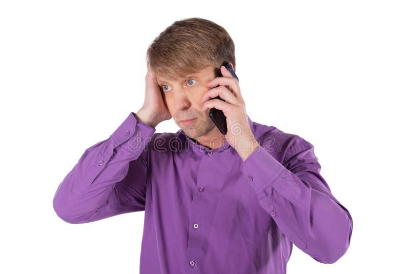 Uomo stupito di medio evo che parla sul telefono su fondo bianco fotografie stock