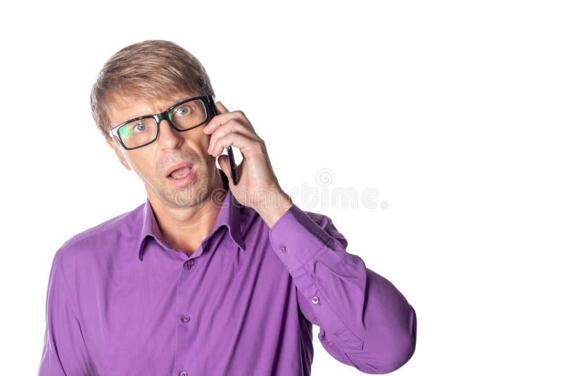 Uomo stupito di medio evo con i vetri che parla sul telefono su fondo bianco immagini stock