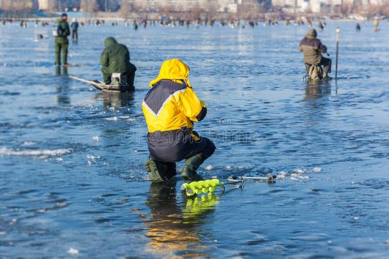 Uomo su pesca di inverno, la gente sul ghiaccio del lago congelato, fis immagini stock libere da diritti