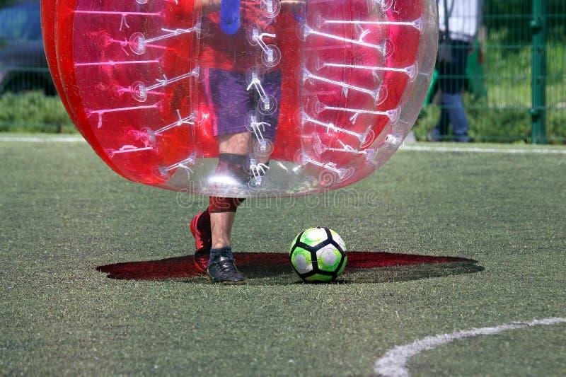 Uomo su un campo sportivo che gioca nella palla del paraurti immagini stock