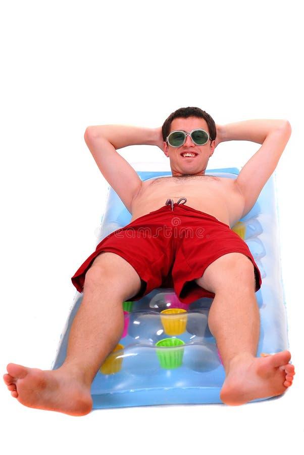 Uomo su un materasso acquatico immagini stock
