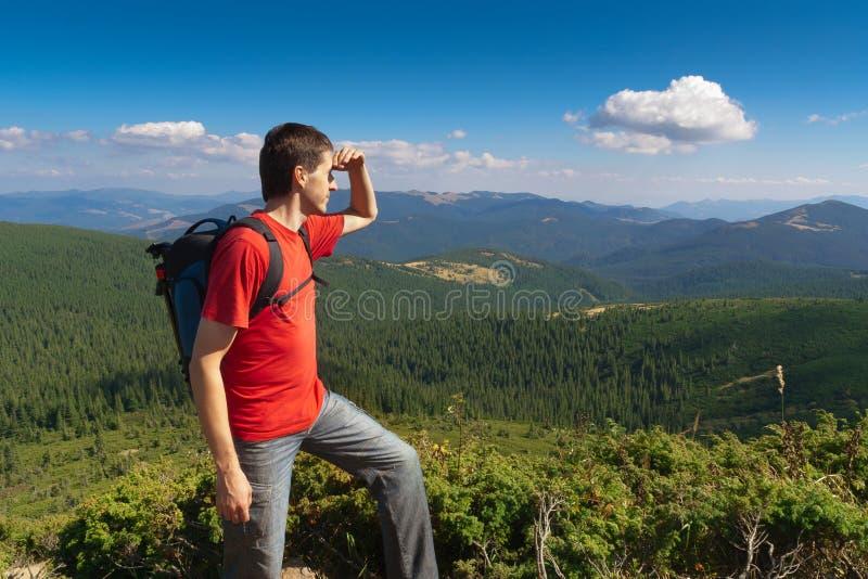 Uomo su un picco delle montagne e di sguardo del paesaggio fotografia stock libera da diritti