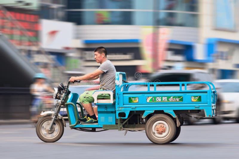 Uomo su una bici elettrica del trasporto a Pechino del centro, Cina immagini stock
