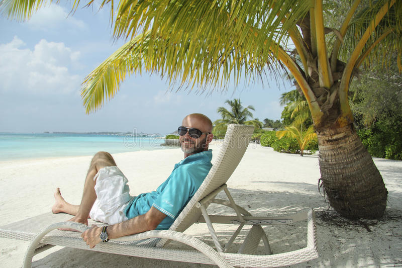 Uomo su una chaise-lounge del sole sotto la palma nella spiaggia delle Maldive immagine stock libera da diritti