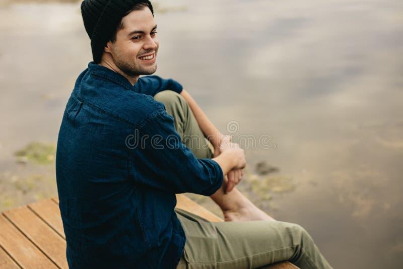 Uomo su una festa che si siede vicino ad un lago fotografie stock libere da diritti